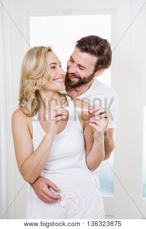 Happy couple checking pregnancy test in bathroom
