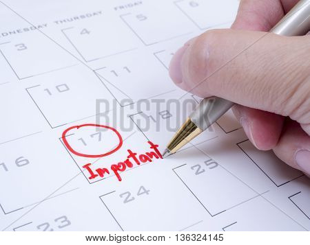 Woman hold a pen on right hand and handwriting word important on calendar desk with red ink