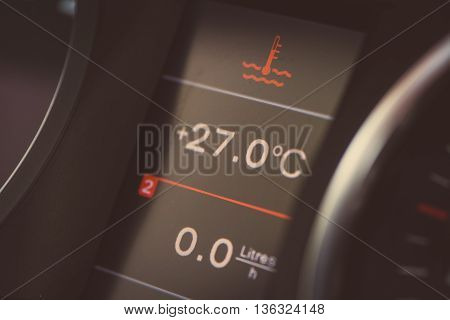 Close up shot of a car's electronic dashboard with coolant warning on.