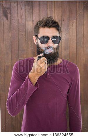 Hipster man smoking the pipe at work