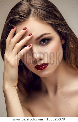 Fashion portrait of gorgeous young blond woman with red lips and nails. Shallow depth of field. With fingers on forehead