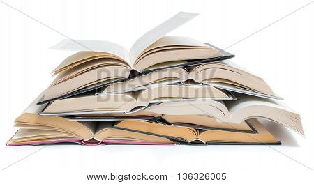Many opened stacked books isolated on white background.