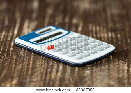 Electronic calculator on wooden background. Selective focus.
