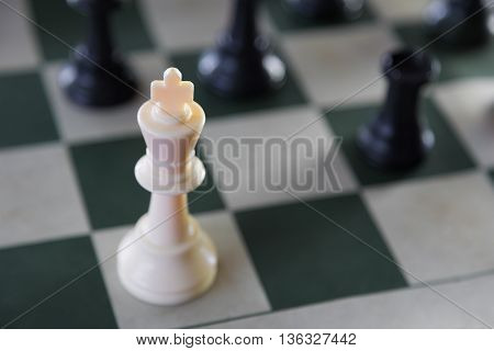 White chess king alone surrounded by the opposite pieces selective focus on white chess king piece