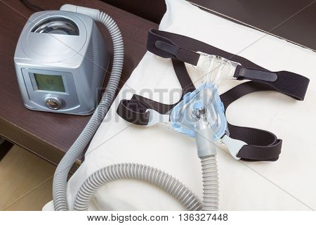 Sleep apnea CPAP headgear mask and hose on white pillow attaching to CPAP machine for people with sleep apnea or sleep disorder