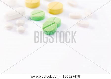 Medicine pills in various shapes colors and sizes on white background with selective focus on the front green pill blur background hard and low angle back lighting to create hard long shadows copyspace for text at bottom of frame