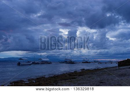 stormy dark sunset in tropical sea with fishing and diving wooden boat near stone coastline and