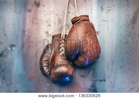 Pair of brown vintage boxing gloves hanging on a metal wall. Copy space.