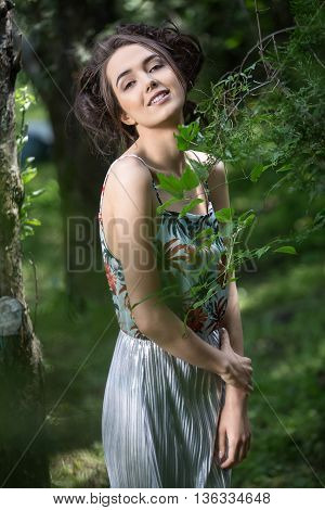Smiling girl in a dress stands partially sideways near the tree on the background of trees. Dress is with silver bottom and flowered top. She holds her hands in front of herself, right hand is on the left forearm. She looks into the camera. Vertical.