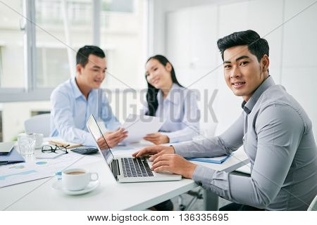 Portrait of young Vietnamese businessman working on laptop in office
