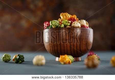 Colored popcorn in wooden bowl. Shallow DOF
