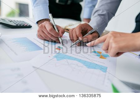 Close-up image of business people analyzing charts and graphs