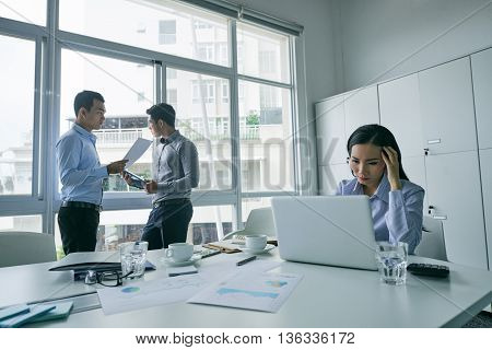 Young business lady working on laptop in modern office