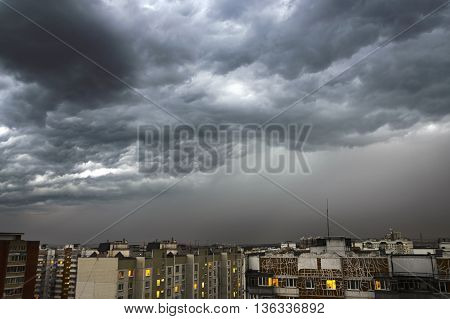 Dark and powerful storm clouds over the city. Heavy rain night shot. Very little light.