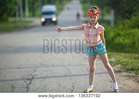 Little funny girl hitchhiker standing on the road.
