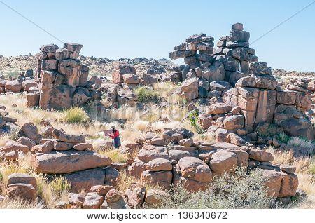 KEETMANSHOOP NAMIBIA - MAY 15 2011: An unidentified artist at work between rock formations at Giants playground near Keetmanshoop