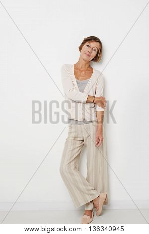 Portrait of mature woman in casual clothes leaning on wall
