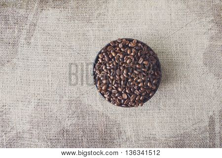 Burlap texture with coffee crop in a bowl background, plenty of robusta beans in plate. Sack cloth canvas with copy space. Heap of seeds at hessian textile, soft toning