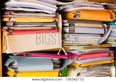 Two stacks of colorful folders and documents at home