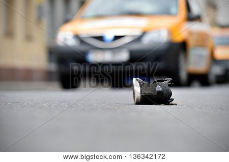 Shoe on the street with cars in background after victim was hit by vehicle