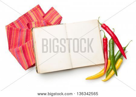 Old cookbook and different colors chilli peppers isolated on white background.