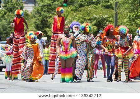 ATLANTA, GA - MAY 2016:  People wearing colorful clown costumes and walking on stilts participate in a parade celebrating Caribbean culture on North Avenue in Atlanta GA on May 28 2016 A.