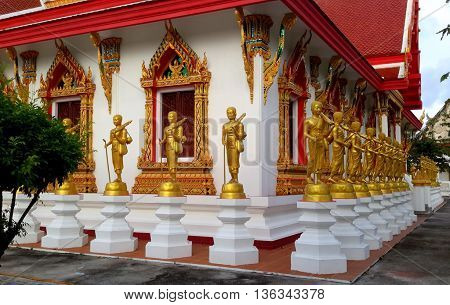 standing golden Buddha statues surrounding Buddhist temple building, Songkhla, Thailand