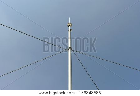 Lightning rod tied with cables against blue sky