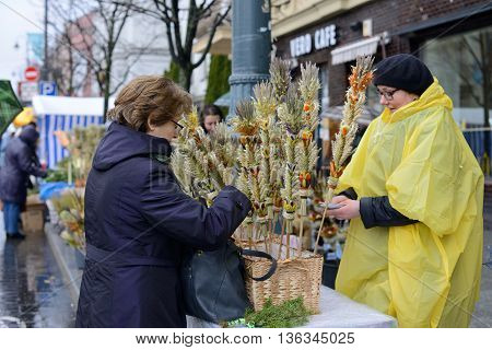 VILNIUS LITHUANIA - MARCH 29: Unidentified people's trades traditional palm bouquets on Palm Sunday fair on March 29 2015 in Vilnius Lithuania.