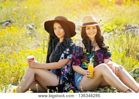 Two beautiful young boho sisters drinking fresh juice and coffee outdoors in summer, sitting in meadow. Two young hippie styled women in floral print and denim outfit, enjoying in nature.