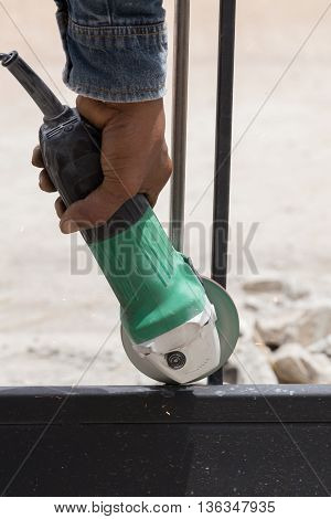 Worker Using An Angle Grinder To Grinding Door Frames