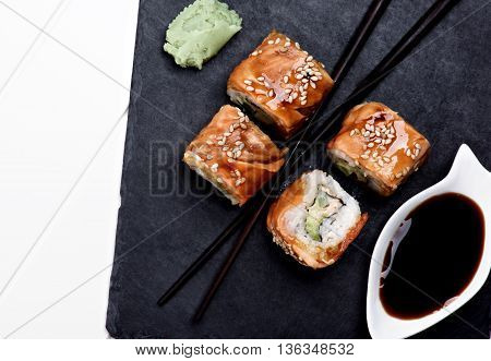 Arrangement of Smoked Eel Sushi with Soy Sauce Wasabi and Chopsticks on Stone Plate closeup on White Plank background. Top View