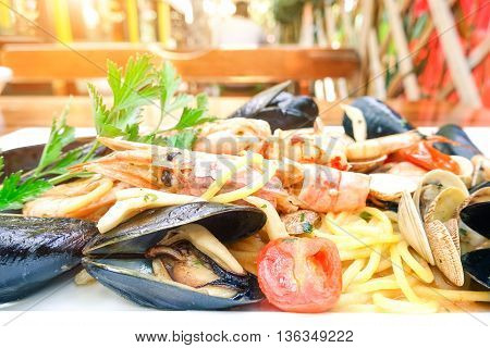 Spaghetti seafood at restaurant closeup side view - Italian sea food noodles dish on table with blurred people background -