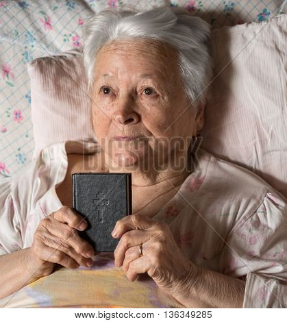 Old woman with Bible in bed at home