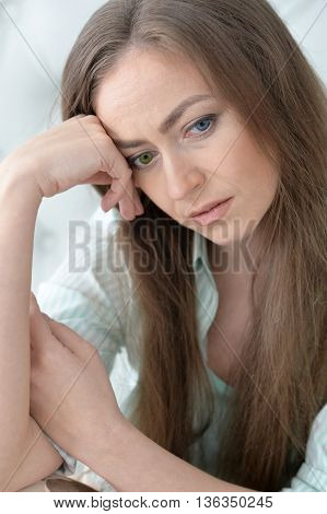 Portrait of a thoughtful woman on background