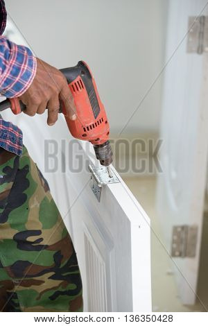 Door Installation. Worker Drills A Hole For Bolt Of Hinge