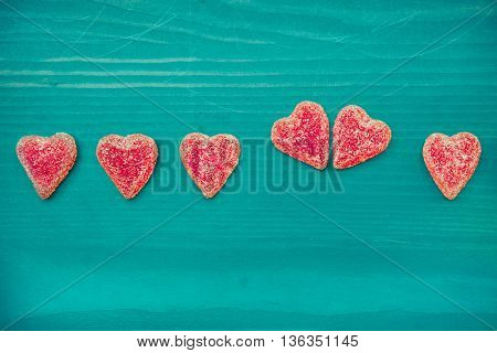 Red sugar valentines day candy hearts on wooden turquoise table. Background. Copy space