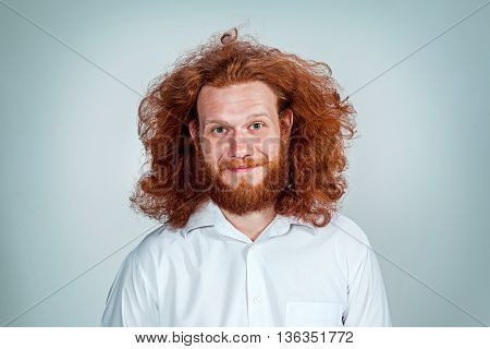 The young smiling man with long red hair looking at camera