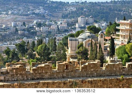 The morning sun illuminates the dome. The Church  in Jerusalem. Battlements of Jerusalem surrounded by majestic building.  On the wall is fenced path for walks