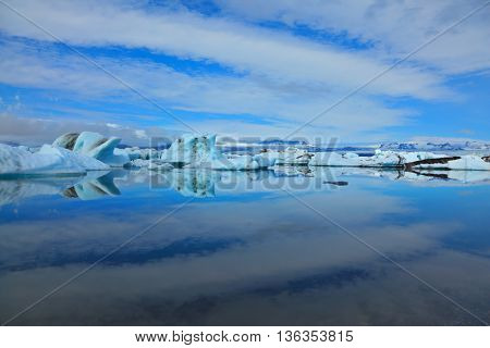 Blue and turquoise icebergs and cirrus clouds are reflected in the Bay Yokulsarlon in Iceland. Sunrise. Reflection
