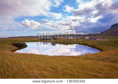 Small pond in the fishing settlement of Arnastapi. Quiet summer evening on the coast of Iceland