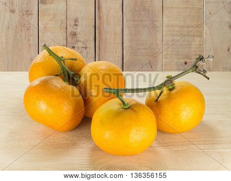 oranges on the wooden table on the wooden panel texture