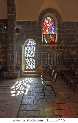 TABGHA, ISRAEL - JANUARY 2012: The interior of ancient church on the shore of Sea of â??â??Galilee. Magnificent stained glass window and glass door illuminated by the sun.