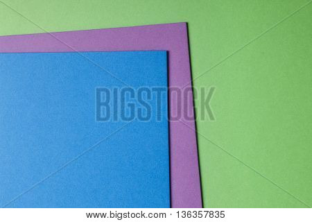 Colored cardboards background in blue purple green tone. Copy space. Horizontal