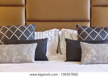 Brown leather bed head detail with cushions. Horizontal