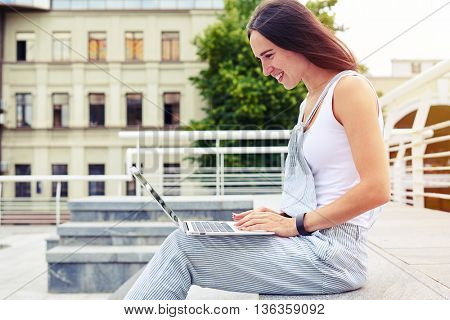 Side view of young attractive female in overalls working on laptop in the city