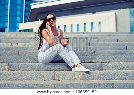 Young attractive smiling lady is sitting on the city stairs with a cup of coffee to go and talking on the phone