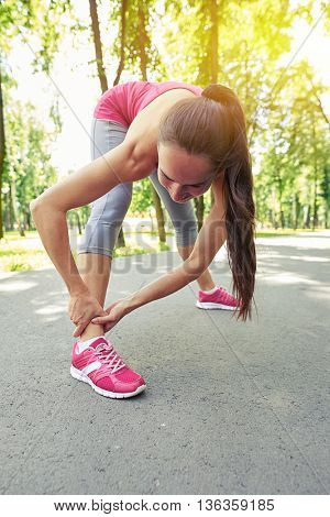 Young slim beautiful woman is doing legs workout after jogging in the park