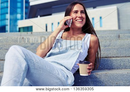 Close-up of young attractive female who is resting on city stairs with a cup of coffee to go and talking on the phone