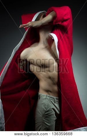 sexual young new year man with muscular body in red christmas santa coat posing on studio background
